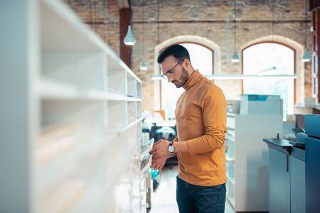 Standing near shelves. Handsome stylish writer wearing orange polo neck standing near shelves