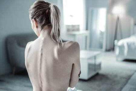 Sporty body. Attentive girl turning head while demonstrating her back
