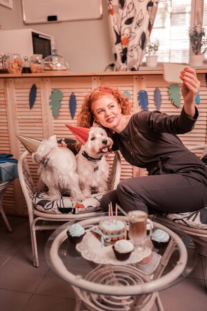 Selfie with dogs. Beaming red-haired woman loving dogs greatly making selfie with her cuties