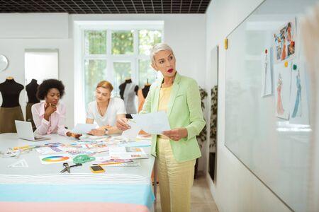 Stilvolle Frau. Modische ältere blonde Frau, die in einer Werkstatt steht, während sie Skizzen hält und in die Ferne schaut