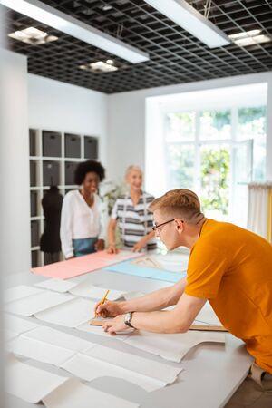 Lieblingsbeschäftigung. Blonder junger männlicher Modedesigner, der in einem Studio arbeitet und ein neues Kleidermuster zeichnet