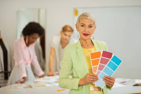 Color samples. Closeup portrait of a senior female fashion designer standing in a workshop while holding color samples