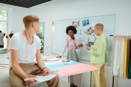 Creative people. Young male fashion designer holding color samples while looking at his colleagues in a studio