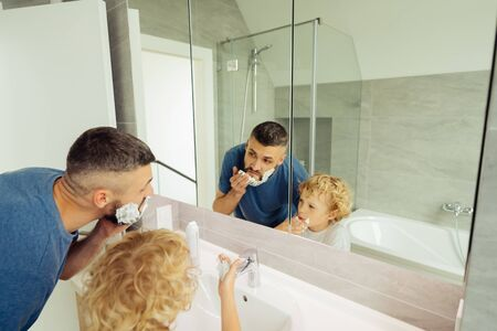 Shaving time. Nice cute father and son looking into the bathroom mirror while shaving together