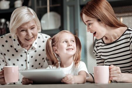 Modern tablet. Positive little girl sitting with her relatives and showing them her modern device Фото со стока