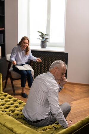 Absorbed in thought. Pensive grey-haired man sitting silently on the sofa and looking down while a blonde woman talking to him