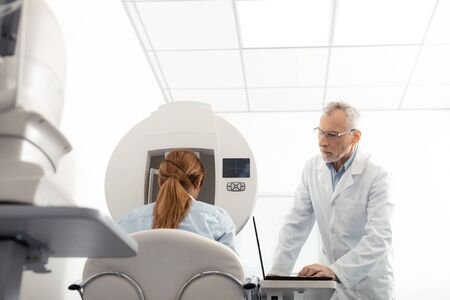 Examining woman attentively. Grey-haired eye specialist wearing glasses examining woman attentively