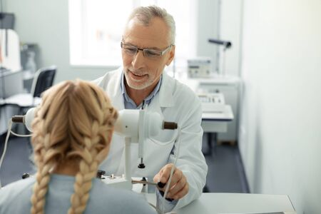 Smiling and speaking. Pleasant grey-haired ophthalmologist smiling and speaking to girl while consulting her Stock fotó