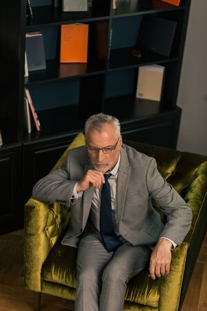 In an armchair. Thoughtful serious grey-haired man sitting in an olive green armchair while propping his chin