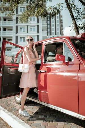 Great talker. Smiling pretty woman talking on her phone getting into the red retro-car before the car ride.