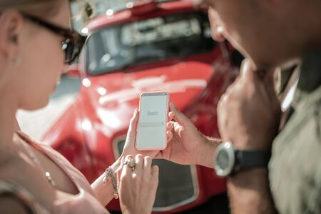 Internet search. Concentrated married couple holding a smartphone together being in search of information about their new car. Standard-Bild