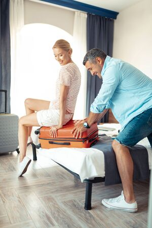 Helping hand. Smiling woman sitting on top of the suitcase helping her concentrated husband with packing and closing it. Stockfoto