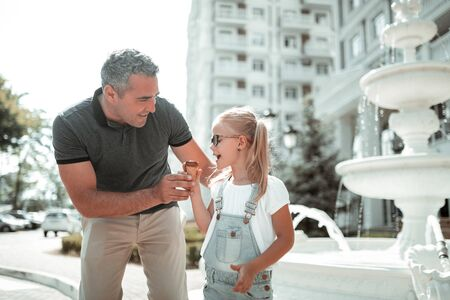 Father-daughter time. Happy little girl eating chocolate ice-cream walking with her smiling dad hugging her. Foto de archivo