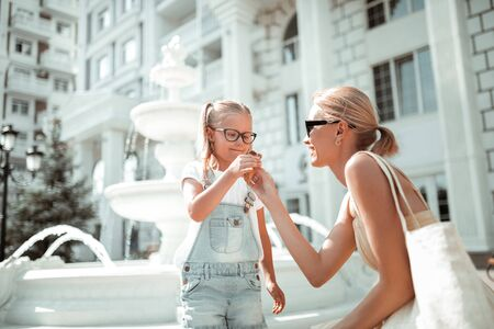 Spending time with mom. Mother giving her daughter an ice-cream cone during their walk together in the summer morning.
