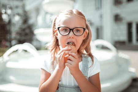 Sweet childhood. Serious bespectacled little girl eating her chocolate ice-cream cone outside holding it with two hands.