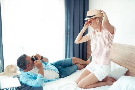 Like a model. Beautiful woman wearing a straw hat and heart-shaped sunglasses posing for her husband with a camera.