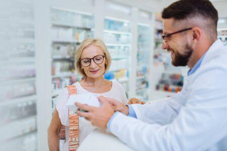 Nueva medicina. Foto de perfil del joven químico que mantiene una sonrisa en su rostro mientras demuestra el paquete Foto de archivo