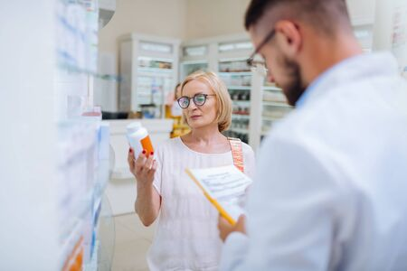 Certificated medicine. Serious mature client wearing glasses while holding bottle with vitamins