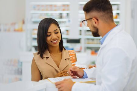 Dark-haired female. Cheerful girl expressing positivity while looking at prescription Фото со стока