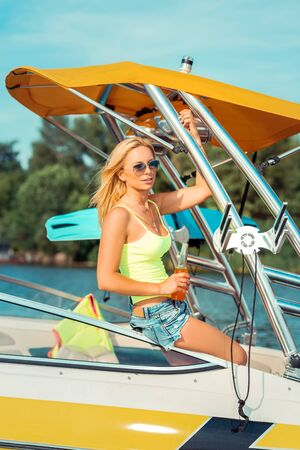 Pretty blonde. Pretty Caucasian blonde girl holding a bottle of soft drink while sitting in a pleasure boat