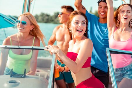 Laughing company. Happy young girl with a bottle in her hand standing at the steering wheel on a yacht while her friends dancing during a party Stockfoto