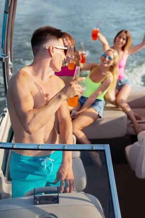 Heres to you. Dark-haired smiling young man looking over his shoulder at three cheerful girls sitting on the deck behind him and drinking soft beverages