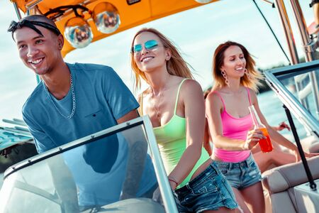 Man at the wheel. Happy young man and his girlfriend standing at the steering wheel while driving a pleasure boat looking ahead