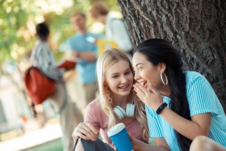 Sharing opinions. Two smiling gossip girls whispering and talking about their friends sitting close to each other under the big tree. Banque d'images