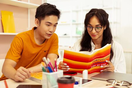 Learning together. Emotional Asian man sitting near his friend while staring at book Stockfoto