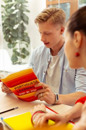 Practical use. Kind young man leaning arms on table while reading book in foreign language