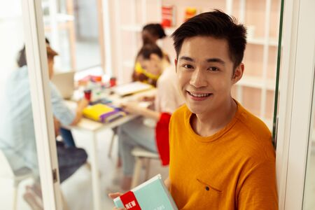 Being satisfied. Cheerful Asian man standing near his classroom while going to practice foreign language Stockfoto