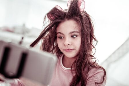 My hairstyle. Nice beautiful girl wearing hair rollers while looking at her hair