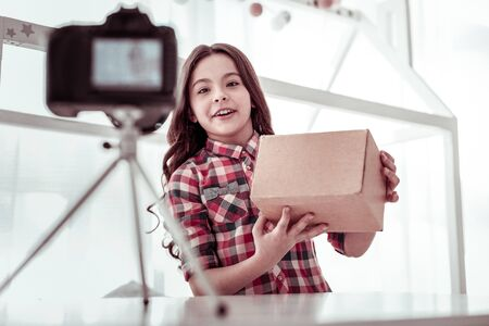 Look what I have. Positive happy girl standing in front of the camera while holding a box