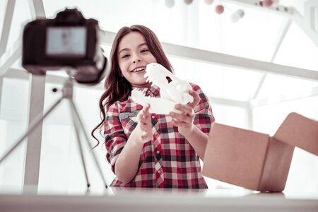 3d modeling. Delighted nice girl standing in front of the camera while playing with a dinosaur model Imagens