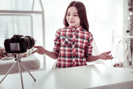 Jonge blogger. Vrolijk positief meisje dat tegen de camera spreekt tijdens het opnemen van een nieuwe video