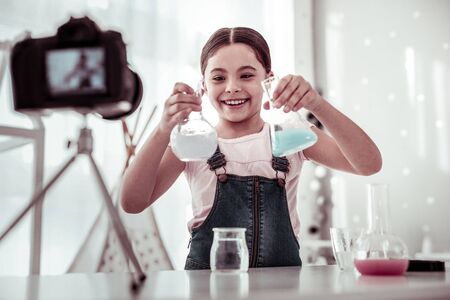 Successful experiment. Joyful happy girl smiling while looking at flasks in her hands