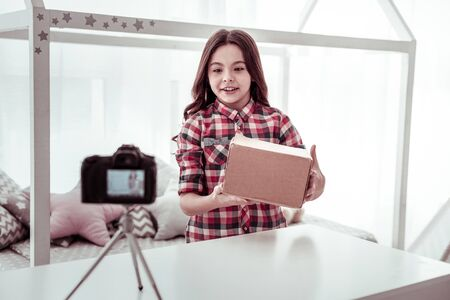 My package. Joyful positive girl looking into the camera while standing with a box