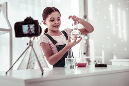 Young genius. Cute smart girl working in the lab while being interested in science