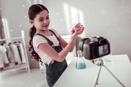 Chemical reagent. Joyful intelligent girl holding a small flask with pink piqued while conducting chemical experiments at home