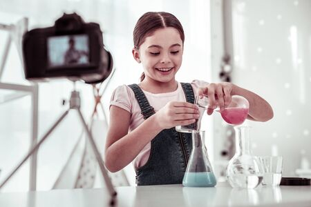 Innovative solutions. Happy joyful girl mixing different liquids while being interested in her chemical experiment