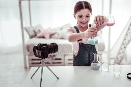 Young chemist. Joyful nice girl pouring liquid from one flask to another while conducting a scientific experiment