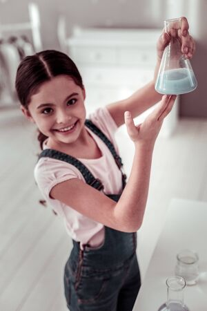 Chemistry lesson. Selective focus of a flask with bleu liquid being in hands of a positive smart girl