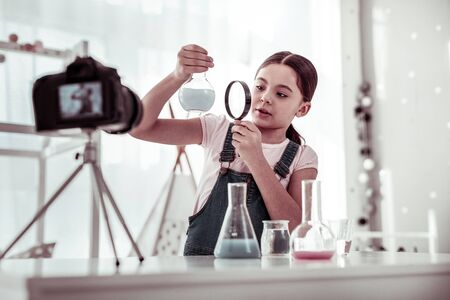 Young scientist. Pleasant smart young girl holding magnifying glass while looking at the flask