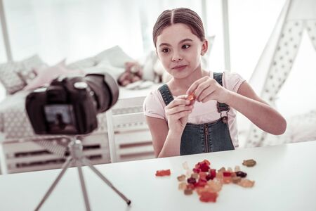 Favourite sweets. Joyful nice girl holding a gummy bear while taking a video