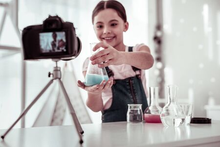 Chemistry research. Selective focus of a flask in girls hands being shown to the camera
