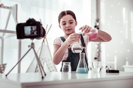 Chemistry blog. Pleasant smart girl conducting an experiment while recording a new video for her chemistry blog