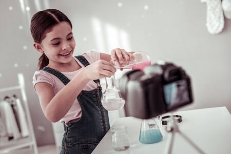 Best subject. Cheerful curious girl experimenting with different liquids while being interested in chemistry Imagens