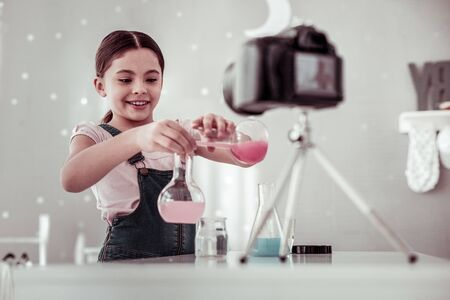 Chemical experiment. Positive smart girl mixing different liquids while conducting a chemical experiment Imagens