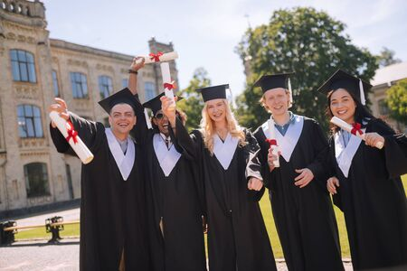 Obtaining the Masters degree. Five cheerful students standing together in the campus celebrating their graduation from the university.