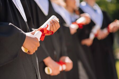 Important documents. Hands of graduates holding their rolled diplomas with red ribbons on them. Banco de Imagens